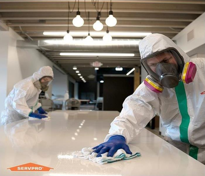 technicians wiping and disinfecting touchable surfaces
